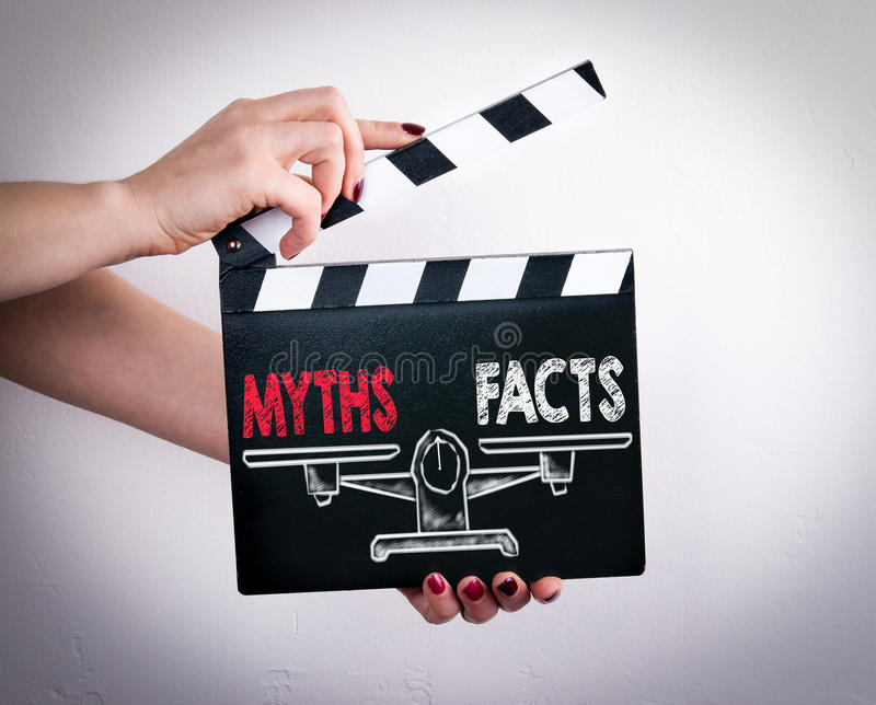 Μύθοι εναντίον της ισορροπίας γεγονότων Θηλυκά χέρια που κρατούν clapper κινηματογράφων στοκ φωτογραφία με δικαίωμα ελεύθερης χρήσης