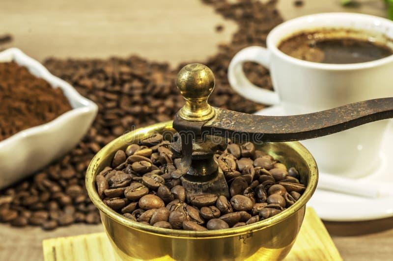 Μύλος καφέ με τα φασόλια καφέ, το φλιτζάνι του καφέ και τον επίγειο καφέ στοκ εικόνες
