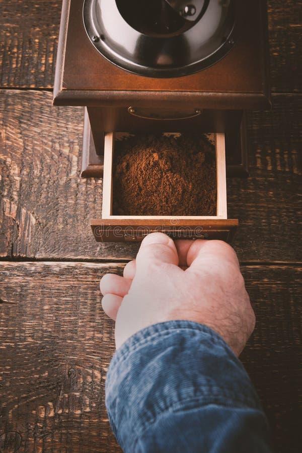 Μύλος καφέ με το χέρι στην ξύλινη επιτραπέζια κατακόρυφο στοκ εικόνα με δικαίωμα ελεύθερης χρήσης