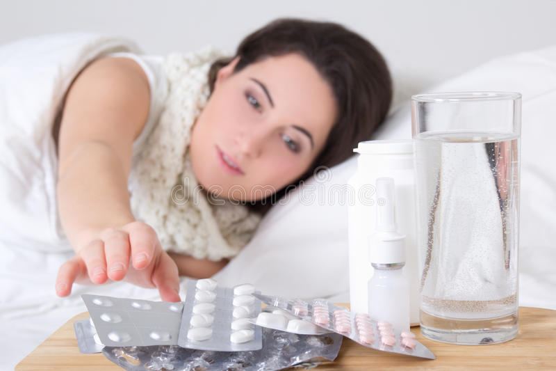 Νέα άρρωστη γυναίκα στο κρεβάτι και χάπια στον πίνακα πλευρών στοκ φωτογραφία