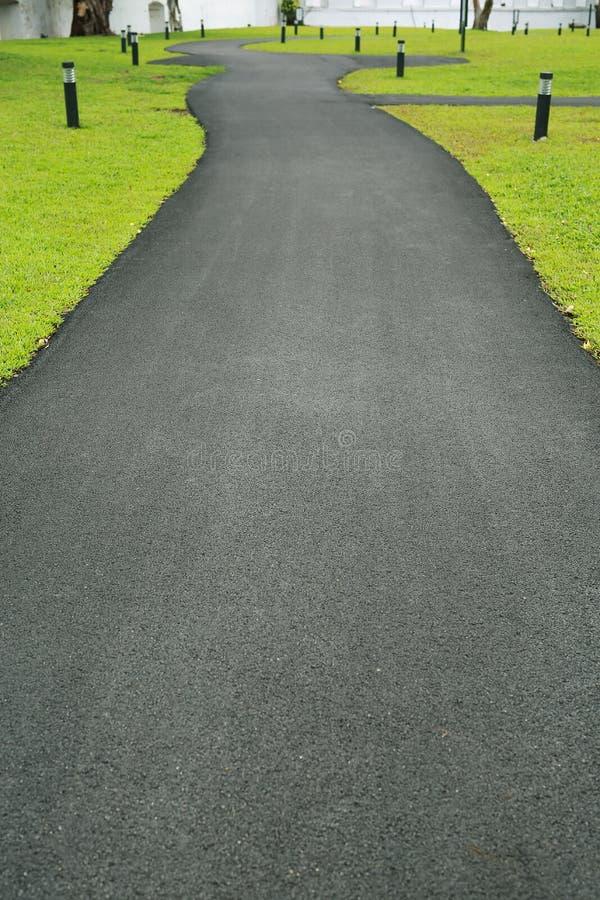 Νέα άσφαλτος που είναι ομαλά οδική διάβαση πεζών στον πράσινο κήπο χλόης στοκ φωτογραφίες με δικαίωμα ελεύθερης χρήσης
