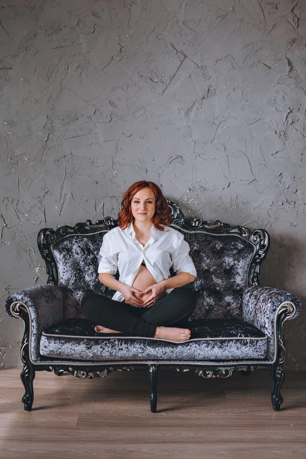 Νέα έγκυος γυναίκα με την κόκκινη συνεδρίαση τρίχας σε έναν γκρίζο καναπέ στο μπαρόκ ύφος Αυτή ` s που φορά ένα άσπρο πουκάμισο,  στοκ εικόνα με δικαίωμα ελεύθερης χρήσης