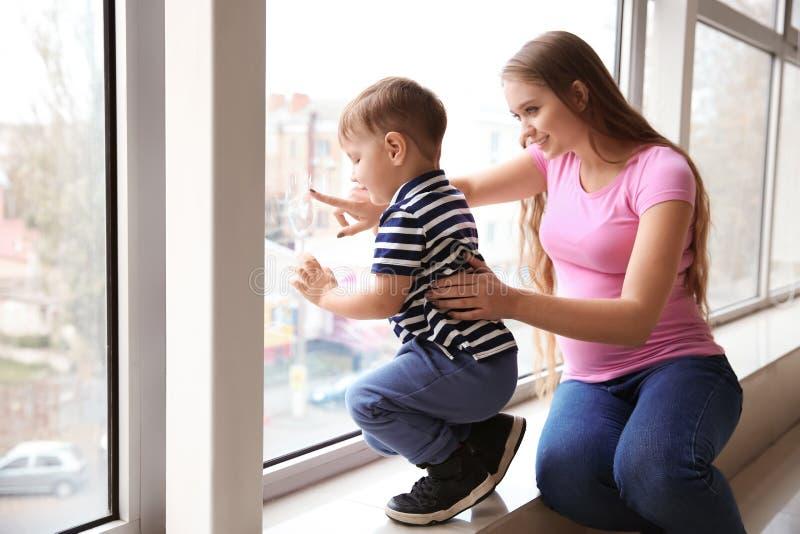 Νέα έγκυος γυναίκα με το χαριτωμένο μικρό γιο της κοντά στο παράθυρο στοκ εικόνες