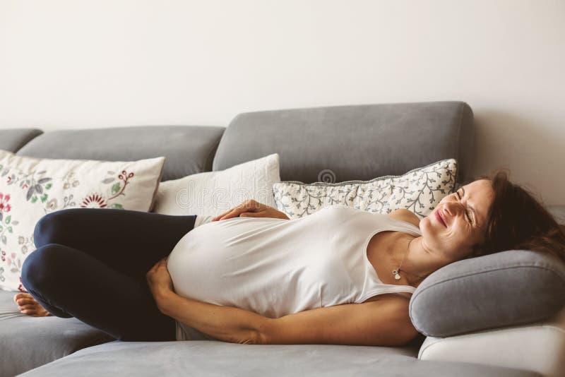 Νέα έγκυος γυναίκα, που έχει την επίπονη συστολή, που αρχίζει την εργασία στοκ φωτογραφία με δικαίωμα ελεύθερης χρήσης