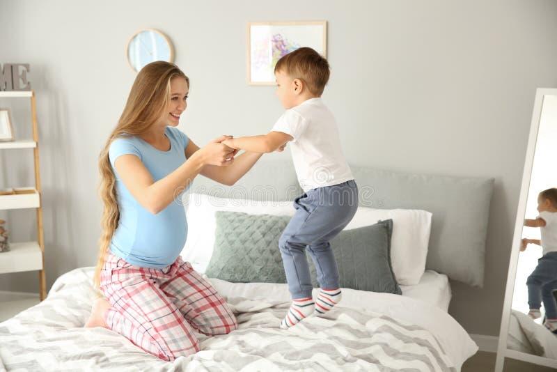 Νέα έγκυος γυναίκα που παίζει με την λίγο γιο στο σπίτι στοκ φωτογραφία με δικαίωμα ελεύθερης χρήσης