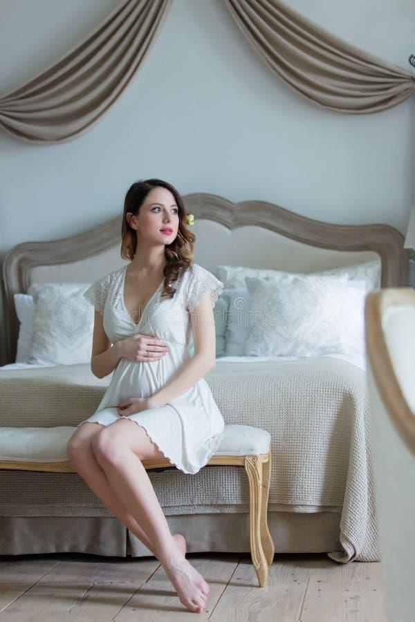 Νέα έγκυος γυναίκα στην άσπρη συνεδρίαση φορεμάτων στοκ φωτογραφίες