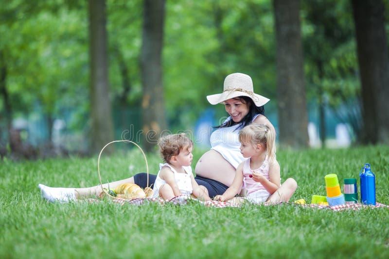 Νέα έγκυος μητέρα με δύο κορίτσια σε ένα παιχνίδι πικ-νίκ στοκ εικόνες με δικαίωμα ελεύθερης χρήσης
