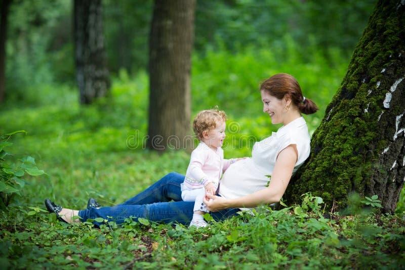 Νέα έγκυος μητέρα με την κόρη μικρών παιδιών της στοκ εικόνες