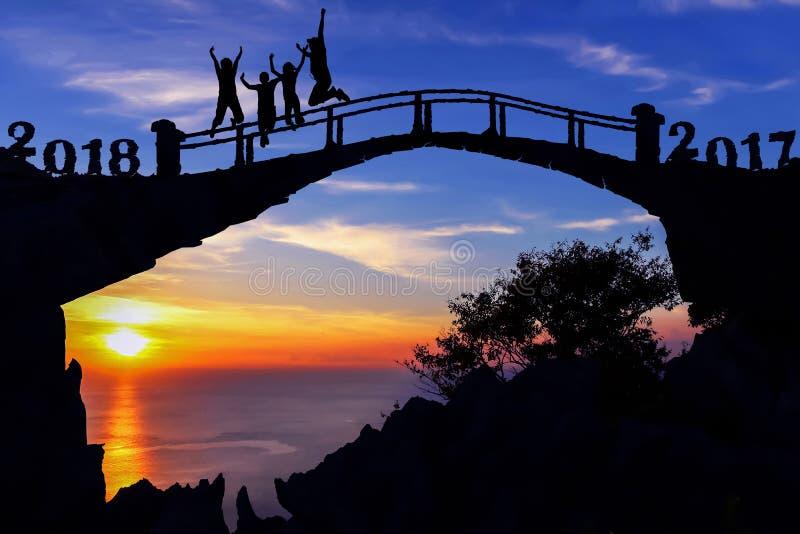 Νέα έννοια έτους 2018 Οικογένεια σκιαγραφιών που πηδά στη γέφυρα στοκ φωτογραφίες