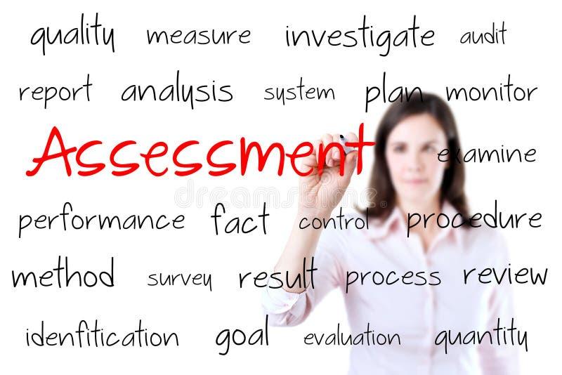 Νέα έννοια αξιολόγησης του γραψίματος επιχειρησιακών γυναικών. Απομονωμένος στο λευκό. στοκ φωτογραφία
