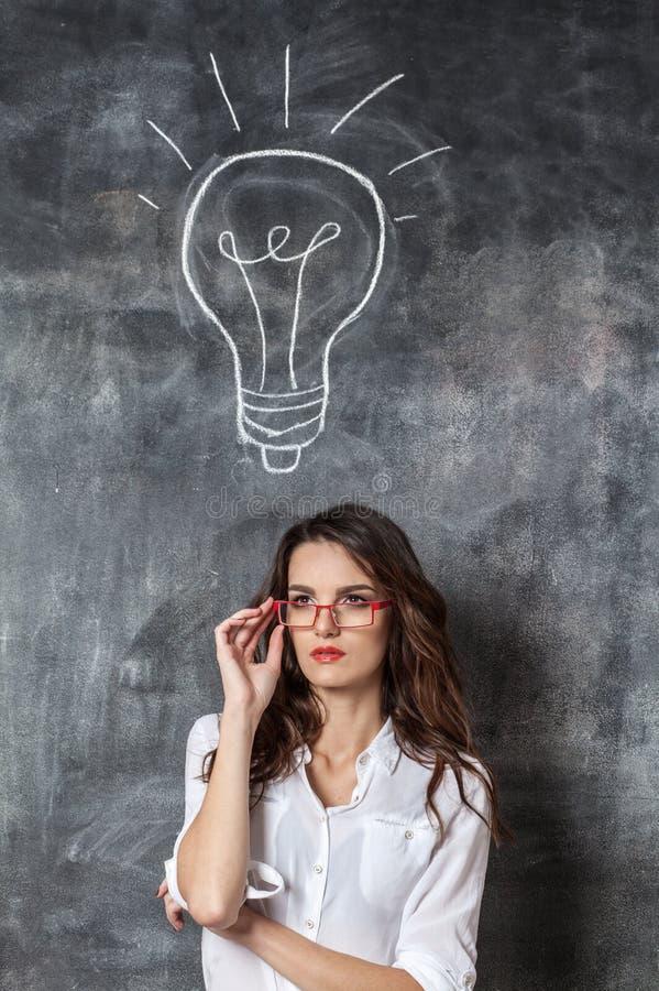 Νέα έξυπνη γυναίκα eyeglasses με το βολβό συμβόλων ιδέας στοκ εικόνες με δικαίωμα ελεύθερης χρήσης