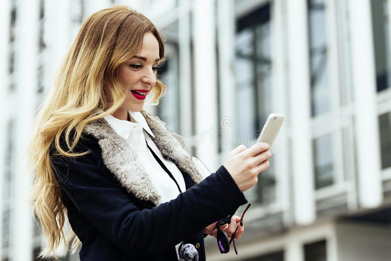 Νέα έξυπνη επαγγελματική ανάγνωση γυναικών που χρησιμοποιεί το τηλέφωνο στοκ φωτογραφία με δικαίωμα ελεύθερης χρήσης