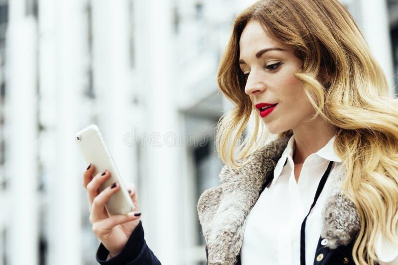 Νέα έξυπνη επαγγελματική ανάγνωση γυναικών που χρησιμοποιεί το τηλέφωνο στοκ εικόνες