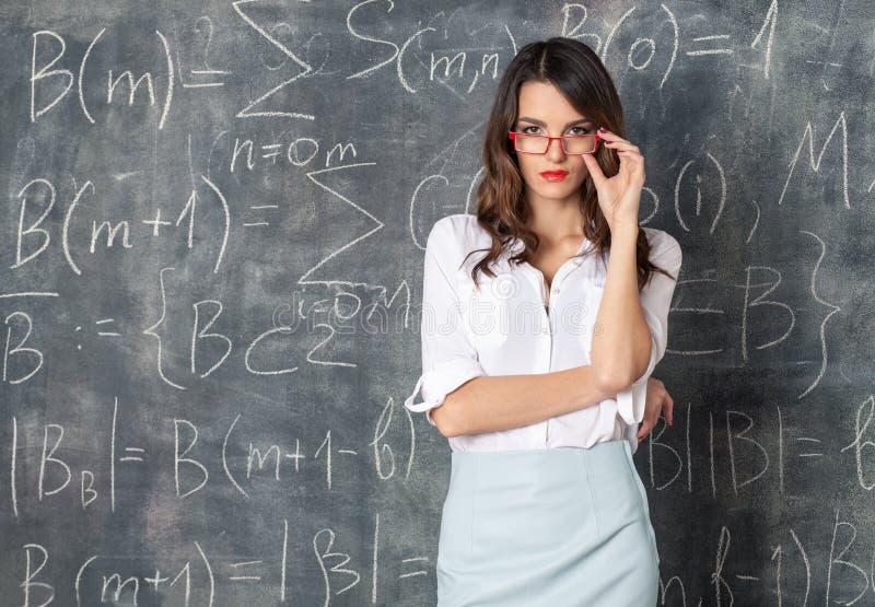 Νέα έξυπνη όμορφη γυναίκα eyeglasses κοντά στον πίνακα στοκ εικόνες με δικαίωμα ελεύθερης χρήσης