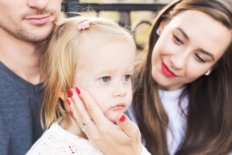 Νέα αγαπώντας οικογένεια τριών, αυθεντικό ειλικρινές υπαίθρια οικογενειακό πορτρέτο στοκ φωτογραφία
