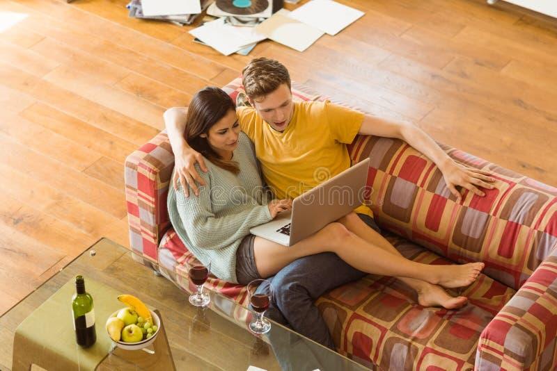 Νέα αγκαλιά ζευγών στον καναπέ με το lap-top στοκ φωτογραφία με δικαίωμα ελεύθερης χρήσης