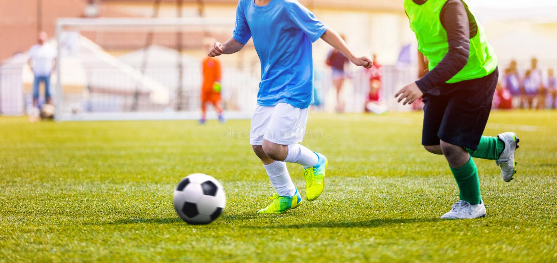 Νέα αγόρια στα μπλε και κίτρινα πουκάμισα του Τζέρσεϋ ποδοσφαίρου και σφήνες ποδοσφαίρου που κλωτσούν τη σφαίρα ποδοσφαίρου στοκ φωτογραφία με δικαίωμα ελεύθερης χρήσης