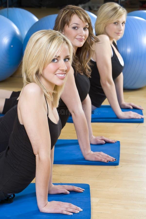 Νέα αεροβική άσκηση γυναικών τρία σε μια γυμναστική στοκ φωτογραφίες