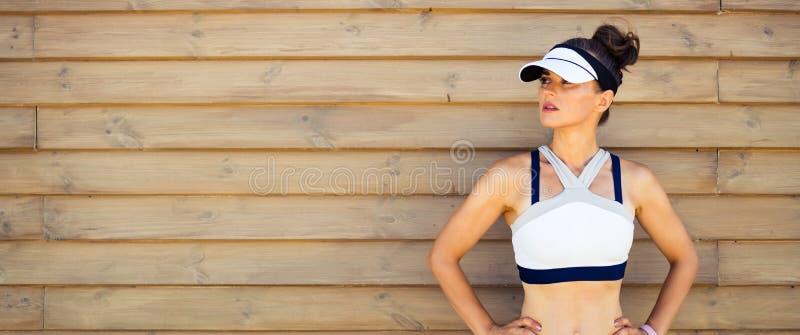 Νέα αθλήτρια που εξετάζει το διάστημα αντιγράφων ενάντια στον ξύλινο τοίχο στοκ εικόνα με δικαίωμα ελεύθερης χρήσης