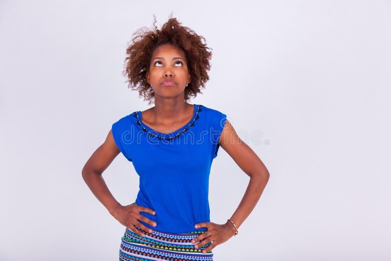 Νέα αμερικανική γυναίκα μαύρων Αφρικανών με το σγοuρό κοίταγμα τρίχας afro στοκ εικόνες