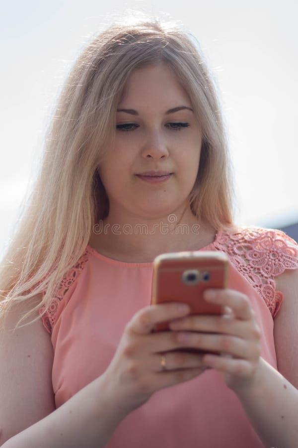 Νέα ανάγνωση γυναικών sms στο κινητό τηλέφωνο στοκ εικόνα με δικαίωμα ελεύθερης χρήσης