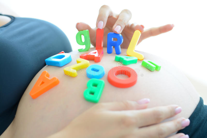 Νέα αναμένουσα μητέρα με τους φραγμούς επιστολών που συλλαβίζει το κορίτσι στην έγκυο κοιλιά της στοκ φωτογραφία με δικαίωμα ελεύθερης χρήσης