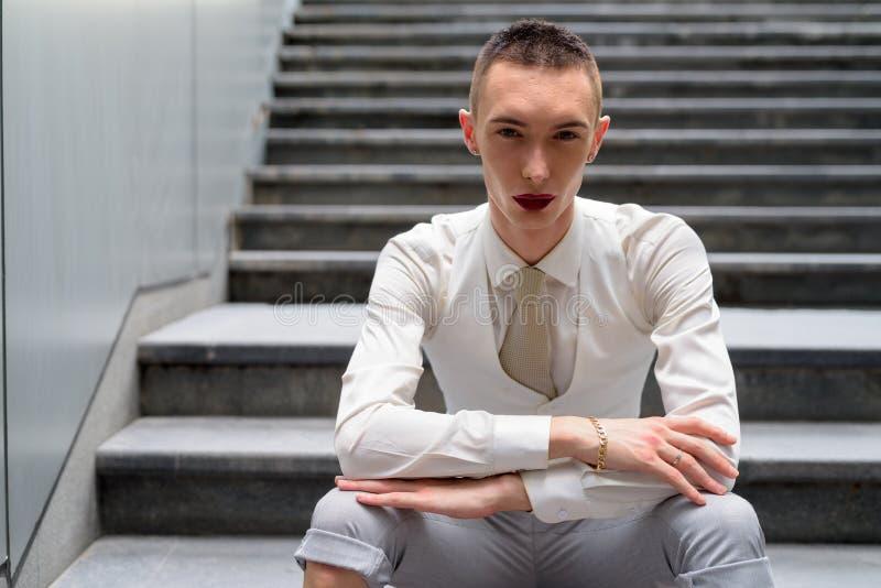 Νέα ανδρόγυνη ομοφυλοφιλική συνεδρίαση επιχειρηματιών LGTB στα σκαλοπάτια στοκ εικόνα