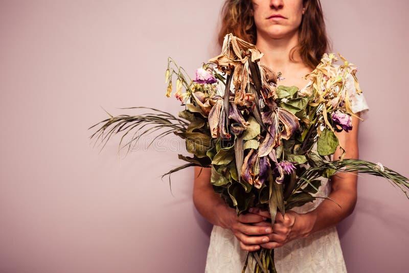 Νέα ανθοδέσμη εκμετάλλευσης γυναικών των νεκρών λουλουδιών στοκ εικόνα