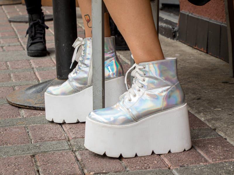 Νέα ανθρώπινα πόδια στις ανυψωμένες μπότες λεσχών σε ένα πεζοδρόμιο τούβλου στοκ φωτογραφίες με δικαίωμα ελεύθερης χρήσης
