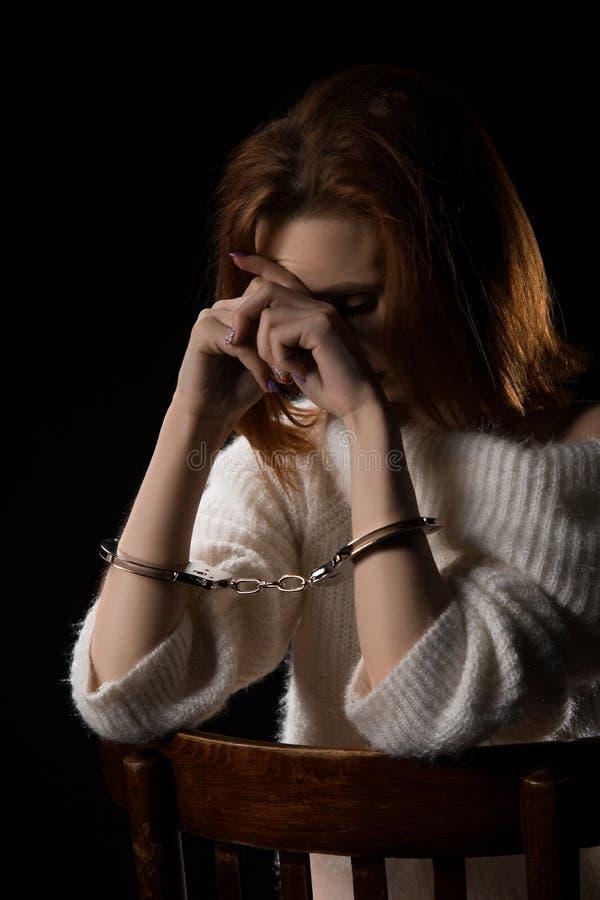 Νέα απαγμένη καταθλιπτική γυναίκα που δένεται με τις χειροπέδες στοκ εικόνα