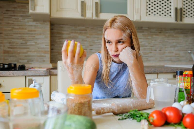 νέα απελπισμένη νοικοκυρά στην κουζίνα της στοκ φωτογραφία