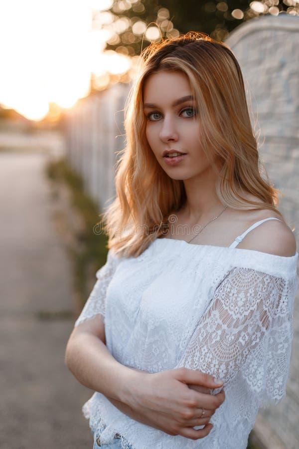 Νέα αρκετά ελκυστική γυναίκα με τα μπλε μάτια με τη φυσική σύνθεση σε μια κομψή δαντελλωτός τοποθέτηση μπλουζών υπαίθρια κοντά σε στοκ εικόνες