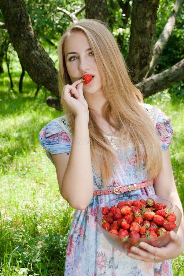 Νέα αρκετά ευτυχής γυναίκα που τρώει τη φράουλα στοκ φωτογραφία με δικαίωμα ελεύθερης χρήσης