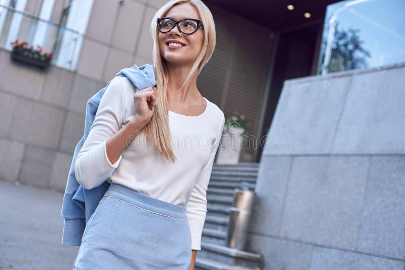 Νέα αρκετά με γυαλιά επιχειρηματίας που χαμογελά και που περπατά κοντά στο επιχειρησιακό κτήριο στοκ εικόνα με δικαίωμα ελεύθερης χρήσης