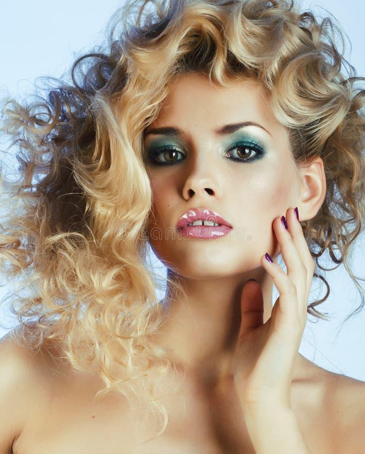 Νέα αρκετά ξανθή γυναίκα με τη σγουρή τοποθέτηση hairstyle ύψους μοντέρνη στην μπλε κινηματογράφηση σε πρώτο πλάνο φορεμάτων στοκ εικόνα