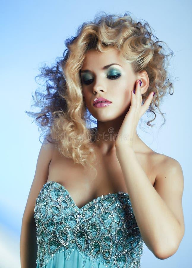 Νέα αρκετά ξανθή γυναίκα με τη σγουρή τοποθέτηση hairstyle ύψους μοντέρνη στην μπλε κινηματογράφηση σε πρώτο πλάνο φορεμάτων στοκ εικόνες με δικαίωμα ελεύθερης χρήσης
