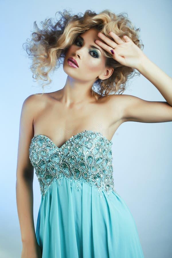 Νέα αρκετά ξανθή γυναίκα με τη σγουρή τοποθέτηση hairstyle ύψους μοντέρνη στην μπλε κινηματογράφηση σε πρώτο πλάνο φορεμάτων στοκ εικόνα με δικαίωμα ελεύθερης χρήσης