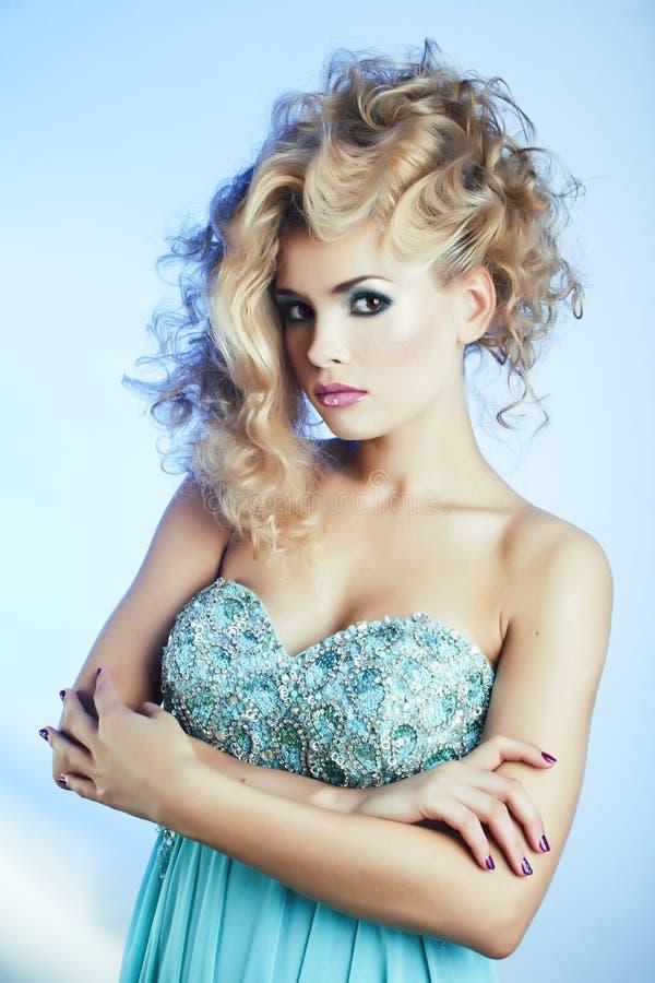 Νέα αρκετά ξανθή γυναίκα με τη σγουρή τοποθέτηση hairstyle ύψους μοντέρνη στην μπλε κινηματογράφηση σε πρώτο πλάνο φορεμάτων στοκ εικόνες