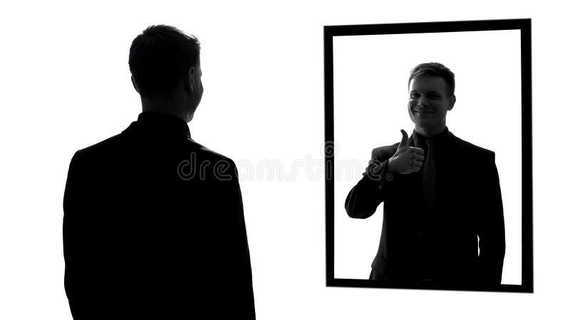 Νέα αρσενική αντανάκλαση που παρουσιάζει αντίχειρες, όμορφος επιτυχής επιχειρηματίας στοκ εικόνα