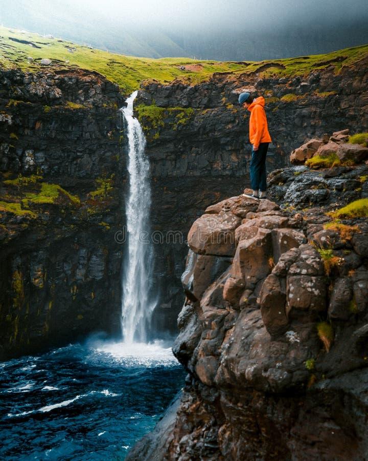 Νέα αρσενική στάση στην άκρη του βράχου με το καταπληκτικό φυσικό τοπίο στο υπόβαθρο στοκ φωτογραφία με δικαίωμα ελεύθερης χρήσης