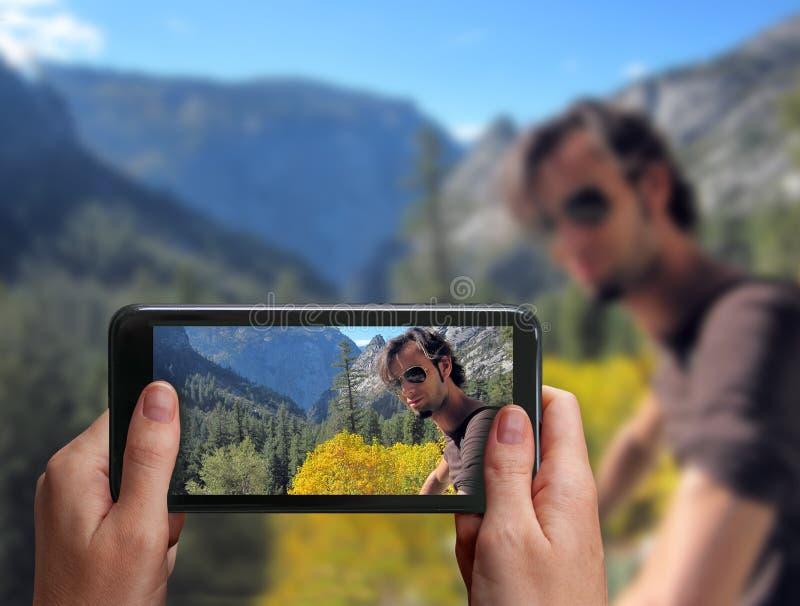 Νέα αρσενική χαλάρωση οδοιπόρων πάνω από ένα βουνό Το χέρι παίρνει μια φωτογραφία με ένα smartphone του ατόμου μαζί W στοκ εικόνα
