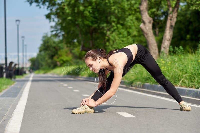 Νέα ασιατικά πόδια τεντώματος γυναικών ικανότητας μετά από το τρέξιμο υπαίθρια αθλητικό πορτρέτο στοκ εικόνα