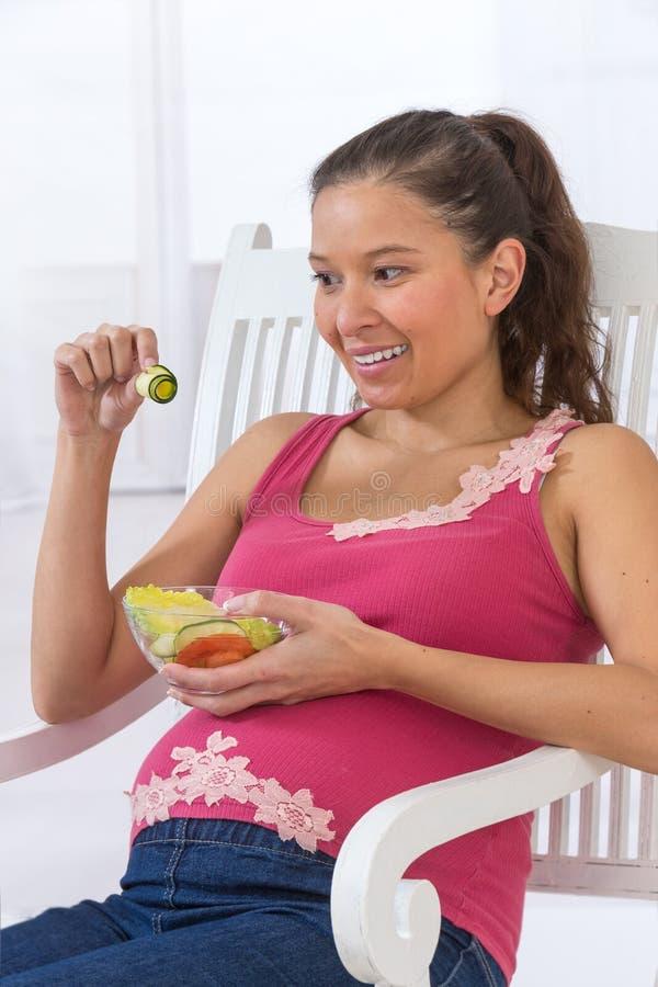 Νέα ασιατική έγκυος γυναίκα που τρώει τη φρέσκια σαλάτα στοκ φωτογραφία