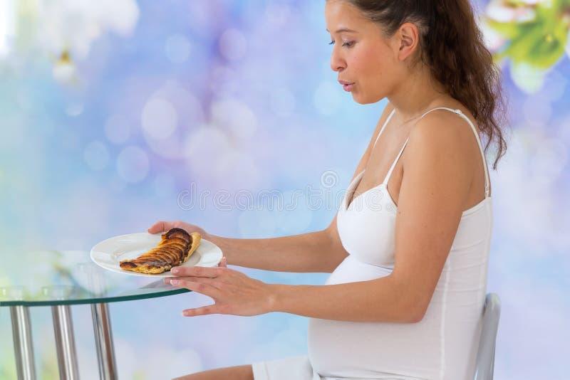 Νέα ασιατική έγκυος γυναίκα που τρώει το γλυκό κέικ στο σπίτι στοκ φωτογραφία