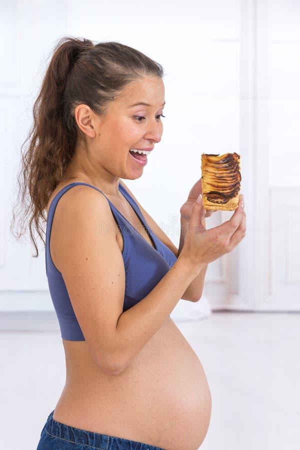 Νέα ασιατική έγκυος γυναίκα που τρώει το γλυκό κέικ στο σπίτι στοκ φωτογραφίες με δικαίωμα ελεύθερης χρήσης