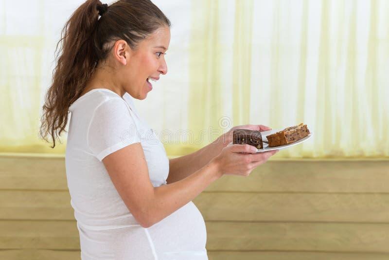 Νέα ασιατική έγκυος γυναίκα που τρώει το γλυκό κέικ στο σπίτι στοκ φωτογραφία με δικαίωμα ελεύθερης χρήσης