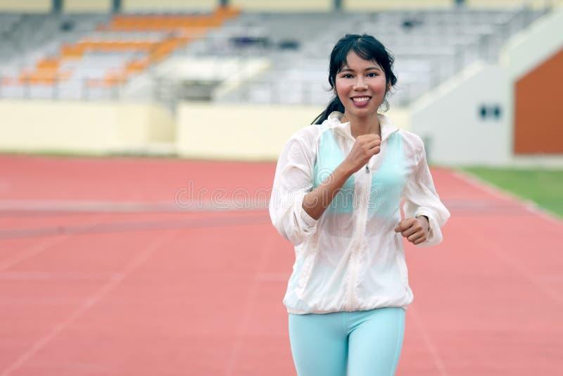 Νέα ασιατική αθλητική πρακτική γυναικών που τρέχει στη διαδρομή στοκ εικόνες