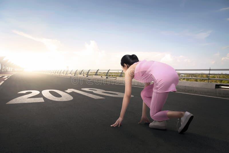 Νέα ασιατική γυναίκα αθλητών έτοιμη στο τρέξιμο με τον αριθμό του 2018 στοκ φωτογραφίες