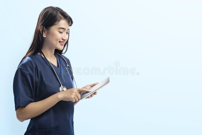 Νέα ασιατική γυναίκα γιατρών με το στηθοσκόπιο που χρησιμοποιεί την ψηφιακή ταμπλέτα στοκ φωτογραφία