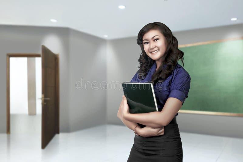 Νέα ασιατική γυναίκα δασκάλων με το βιβλίο στο χέρι της στοκ εικόνα